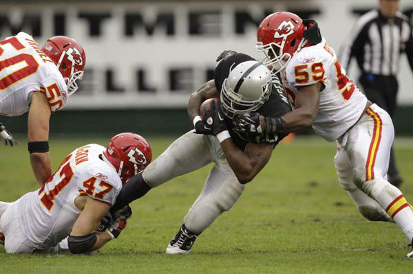 Oakland Raiders running back Darren McFadden &#40;20&#41; is tackled by Kansas City Chiefs linebacker Mike Vrabel &#40;50&#41;, Jon McGraw &#40;47&#41; and  Jovan Belcher &#40;59&#41; during the first quarter of an NFL football game in Oakland, Calif., Sunday, Nov. 7, 2010. &#40;AP Photo&#47;Marcio Jose Sanchez&#41; <span class=meta>(AP Photo&#47; Marcio Jose Sanchez)</span>