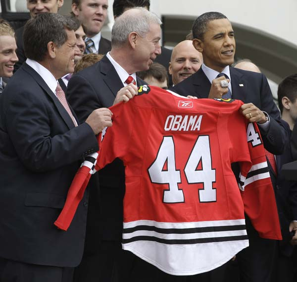 President Barack Obama, right, holds up his championship ring, during a ceremony to honor the 2009-2010 NHL Stanley Cup Champion Chicago Blackhawks in the South Lawn of the White House in Washington, Friday March, 11, 2011. With Obama are Blackhawks president John McDonough, center, and Blackhawks chairman W. Rockwell 'Rocky' Wirtz, left. (AP Photo/Charles Dharapak)