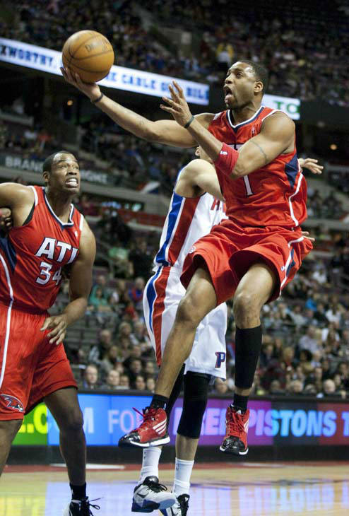 Atlanta Hawks&#39; Tracy McGrady &#40;1&#41; goes past Detroit Pistons&#39; Austin Daye for a basket as Hawks&#39; Jason Collins &#40;34&#41; looks on in the first half of an NBA basketball game on Friday, Jan. 27, 2012, in Auburn Hills, Mich. &#40;AP Photo&#47;Duane Burleson&#41; <span class=meta>(AP Photo&#47; Duane Burleson)</span>