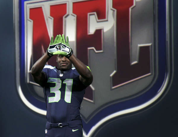 Seattle Seahawks&#39; Kam Chancellor shows off the new design for gloves during a presentation in New York, Tuesday, April 3, 2012.  The NFL and Nike showed off the new look in grand style with a gridiron-styled fashion show at a Brooklyn film studio. &#40;AP Photo&#47;Seth Wenig&#41; <span class=meta>(AP Photo&#47; Seth Wenig)</span>