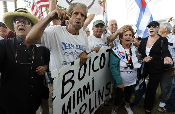 Protestors hold signs outside Marlins Stadium in Miami, where Marlins manager Ozzie Guillen was speaking at a news conference, Tuesday April 10, 2012. Guillen has been suspended for five games because of his comments about Fidel Castro. He has again apologized and says he accepts the punishment.  &#40;AP Photo&#47;Lynne Sladky&#41; <span class=meta>(Photo&#47;Lynne Sladky)</span>