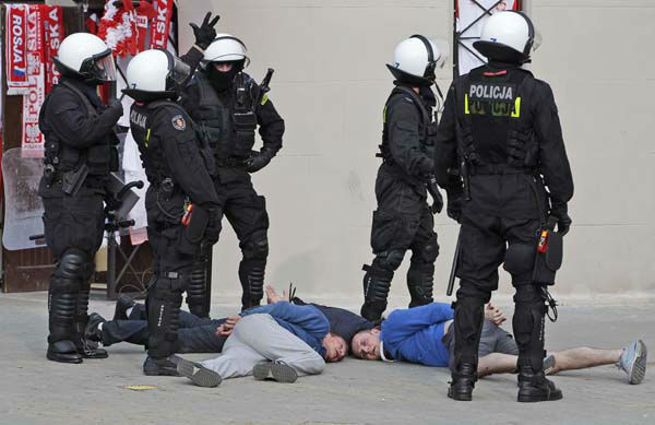 Police guard handcuffed men after they arrested them prior to the Euro 2012 soccer championship Group A match between Poland and Russia in Warsaw, Poland, Tuesday, June 12, 2012. Russian soccer fans clashed with police and Poland supporters in separate incidents in Warsaw on Tuesday, just hours before the two teams were to meet in an emotionally charged European Championship match. Several people were injured. &#40;AP Photo&#47;Gero Breloer&#41; <span class=meta>(AP Photo&#47; Gero Breloer)</span>