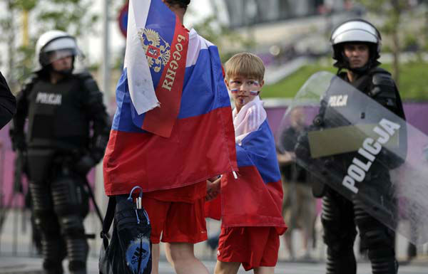 Russian fans arrive under heavy security prior to the Euro 2012 soccer championship Group A match between Poland and Russia in Warsaw, Poland, Tuesday, June 12, 2012. Russian soccer fans clashed with police and Poland supporters in separate incidents in Warsaw on Tuesday, just hours before the two teams were to meet in an emotionally charged European Championship match. Several people were injured. &#40;AP Photo&#47;Gero Breloer&#41; <span class=meta>(AP Photo&#47; Gero Breloer)</span>