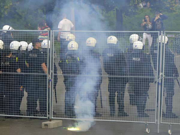 A flare burns behind police officers prior to the Euro 2012 soccer championship Group A match between Poland and Russia in Warsaw, Poland, Tuesday, June 12, 2012. Russian soccer fans clashed with police and Poland supporters in separate incidents in Warsaw on Tuesday, just hours before the two teams were to meet in an emotionally charged European Championship match. Several people were injured. &#40;AP Photo&#47;Alik Keplicz&#41; <span class=meta>(AP Photo&#47; Alik Keplicz)</span>