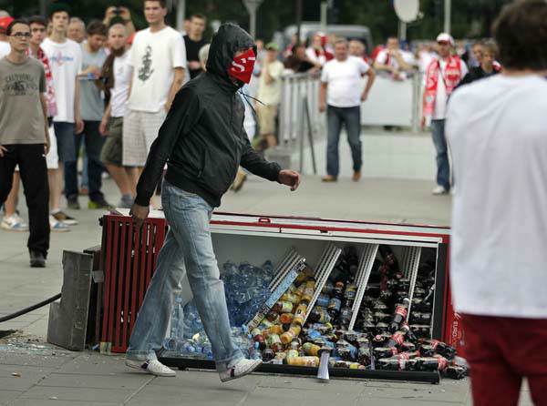 A masked fan walks past a toppled fridge at the Euro 2012 soccer championship Group A match between Poland and Russia in Warsaw, Poland, Tuesday, June 12, 2012. Russian soccer fans clashed with police and Poland supporters in separate incidents in Warsaw on Tuesday, just hours before the two teams were to meet in an emotionally charged European Championship match. Several people were injured. &#40;AP Photo&#47;Gero Breloer&#41; <span class=meta>(AP Photo&#47; Gero Breloer)</span>