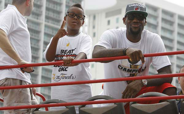 Miami Heat&#39;s LeBron James, right, and his son, Lebron Jr., look out from a doubledecker bus during a parade in celebration of winning the NBA Finals basketball championship against the Oklahoma City Thunder, Monday, June 25, 2012, in Miami. &#40;AP Photo&#47;Lynne Sladky&#41; <span class=meta>(AP Photo&#47; Lynne Sladky)</span>