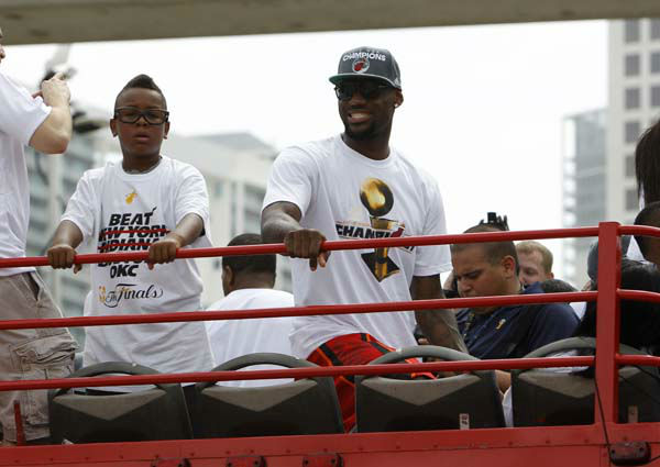 Miami Heat&#39;s LeBron James, right, and his son LeBron Jr., left, look out from a double decker bus during a parade in celebration of winning the NBA Finals basketball championship against the Oklahoma City Thunder, Monday, June 25, 2012, in Miami. &#40;AP Photo&#47;Lynne Sladky&#41; <span class=meta>(AP Photo&#47; Lynne Sladky)</span>