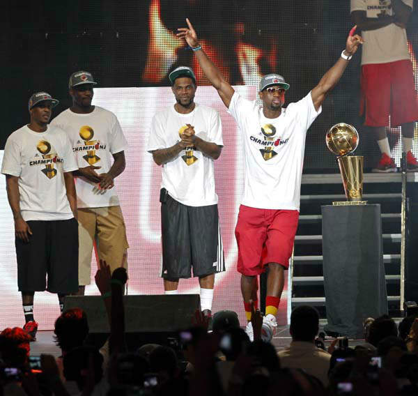 Miami Heat&#39;s Dwyane Wade, right, acknowledges the fans as Mario Chalmers, left, Joel Anthony, second from left, and Udonis Haslem look on in Miami, Monday, June 25, 2012. Thousands of people filled the arena for the Heat NBA Championship celebration.  &#40;AP Photo&#47;Alan Diaz&#41; <span class=meta>(AP Photo&#47; Alan Diaz)</span>