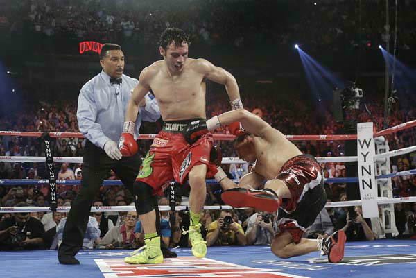 "<div class=""meta ""><span class=""caption-text "">Julio Cesar Chavez Jr., center, knocks Sergio Martinez to the mat for the second time in the 12th round during the WBC middleweight title fight, Saturday, Sept. 15, 2012, in Las Vegas. Martinez won by unanimous decision. (AP Photo/Julie Jacobson) (AP Photo/ Julie Jacobson)</span></div>"