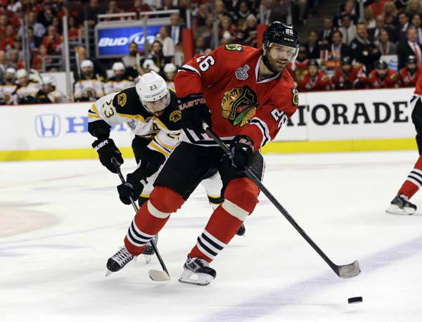 Chicago Blackhawks center Michal Handzus &#40;26&#41; controls the puck against Boston Bruins center Chris Kelly &#40;23&#41; during the first overtime period of Game 1 in their NHL Stanley Cup Final hockey series, Wednesday, June 12, 2013, in Chicago. &#40;AP Photo&#47;Nam Y. Huh&#41; <span class=meta>(AP Photo&#47; Nam Y. Huh)</span>