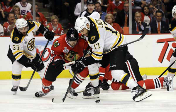 Chicago Blackhawks center Marcus Kruger &#40;16&#41; and Boston Bruins left wing Milan Lucic &#40;17&#41; battle for the control of the puck during the third period of Game 1 in their NHL Stanley Cup Final hockey series, Wednesday, June 12, 2013, in Chicago. &#40;AP Photo&#47;Nam Y. Huh&#41; <span class=meta>(AP Photo&#47; Nam Y. Huh)</span>