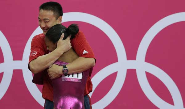 "<div class=""meta ""><span class=""caption-text "">U.S. gymnast Gabrielle Douglas is hugged by coach Liang Chow after her final and deciding performance on the floor during the artistic gymnastics women's individual all-around competition at the 2012 Summer Olympics, Thursday, Aug. 2, 2012, in London.  (AP Photo/Gregory Bull)</span></div>"