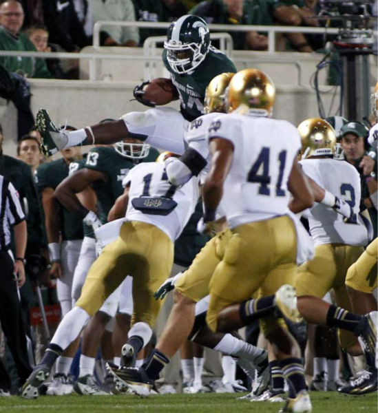 Michigan State&#39;s Le&#39;Veon Bell, top, hurdles Notre Dame&#39;s Zeke Motta &#40;17&#41; during the third quarter of an NCAA college football game, Saturday, Sept. 15, 2012, in East Lansing, Mich. Notre Dame won 20-3. &#40;AP Photo&#47;Al Goldis&#41; <span class=meta>(AP Photo&#47; Al Goldis)</span>