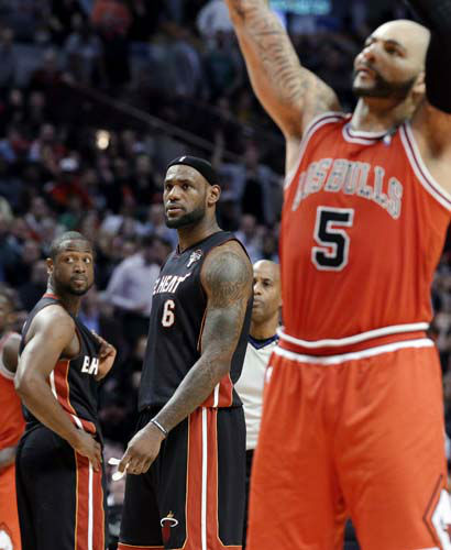 Miami Heat guard Dwyane Wade, left, and forward LeBron James, watch Chicago Bulls forward Carlos Boozer shoot a free throw after James fouled him during the fourth quarter of an NBA basketball game in Chicago on Wednesday, March 27, 2013. The Bulls won 101-97, ending the Heat&#39;s 27-game winning streak. &#40;AP Photo&#47;Nam Y. Huh&#41; <span class=meta>(AP Photo&#47; Nam Y. Huh)</span>