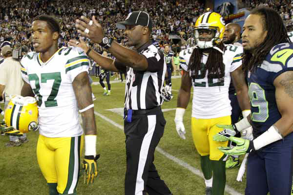An official gestures as Green Bay Packers cornerback Sam Shields &#40;37&#41;, safety Jerron McMillian &#40;22&#41; and Seattle Seahawks free safety Earl Thomas &#40;29&#41; leave the field in the second half of an NFL football game, Monday, Sept. 24, 2012, in Seattle. After a period of confusion, a Seahawks touchdown by wide receiver Golden Tate was allowed to stand for the 14-12 win. &#40;AP Photo&#47;Ted S. Warren&#41; <span class=meta>(AP Photo&#47; Ted S. Warren)</span>