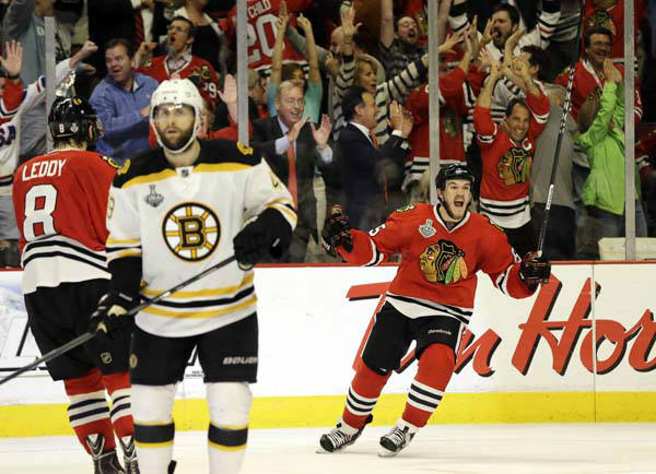 Chicago Blackhawks center Andrew Shaw, right, celebrates after scoring the winning goal during the third overtime period of Game 1 in their NHL Stanley Cup Final hockey series against the Boston Bruins, Thursday, June 13, 2013, in Chicago. &#40;AP Photo&#47;Nam Y. Huh&#41; <span class=meta>(AP Photo&#47; Nam Y. Huh)</span>