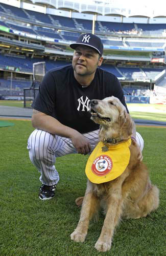 FILE - In this June 4, 2013 file photo, New York Yankees relief pitcher Joba Chamberlain poses  on the field with a golden retriever named Chase that retrieves bats for the Yankees minor league team, the Trenton Thunder, before a baseball game at Yankee Stadium in New York. Chase lived just long enough to be thrown a retirement party by the Trenton Thunder. The party was held at Friday&#39;s game in Trenton, N.J. The team says Chase died Monday, July 8, 2013. &#40;AP Photo&#47;Kathy Willens, File&#41; <span class=meta>(AP Photo&#47; Kathy Willens)</span>