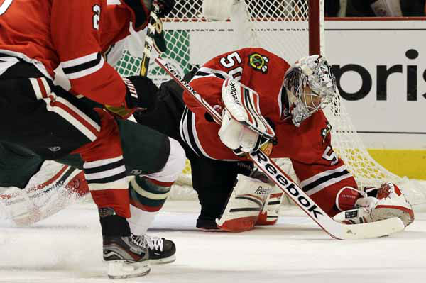 Chicago Blackhawks goalie Corey Crawford, right, saves a shot by Minnesota Wild&#39;s Charlie Coyle &#40;not shown&#41; during the first period of Game 2 of an NHL hockey Stanley Cup first-round playoff series in Chicago, Friday, May 3, 2013. &#40;AP Photo&#47;Nam Y. Huh&#41; <span class=meta>(AP Photo&#47; Nam Y. Huh)</span>