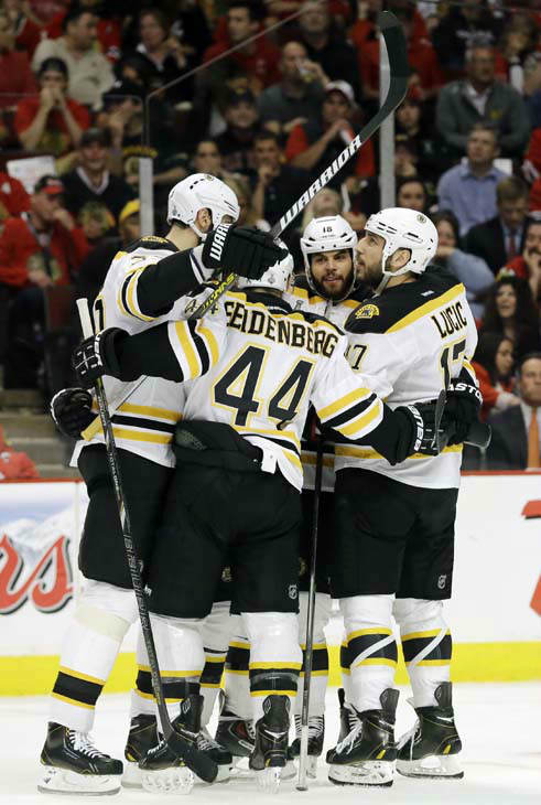 Boston Bruins left wing Milan Lucic, right, celebrates with his teammates including Dennis Seidenberg &#40;44&#41; after scoring a goal against the Chicago Blackhawks during the first period of Game 1 in their NHL Stanley Cup Final hockey series, Wednesday, June 12, 2013, in Chicago. &#40;AP Photo&#47;Nam Y. Huh&#41; <span class=meta>(AP Photo&#47; Nam Y. Huh)</span>