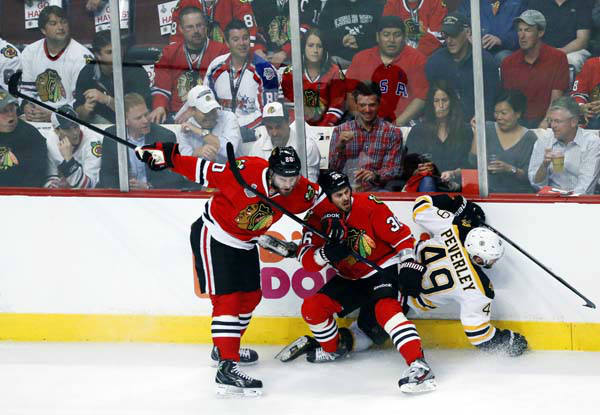 Chicago Blackhawks left wing Brandon Saad &#40;20&#41; and center Dave Bolland &#40;36&#41; collide with Boston Bruins center Rich Peverley &#40;49&#41; during the first period of Game 1 in their NHL Stanley Cup Final hockey series, Wednesday, June 12, 2013 in Chicago. &#40;AP Photo&#47;Charles Rex Arbogast&#41; <span class=meta>(AP Photo&#47; Charles Rex Arbogast)</span>