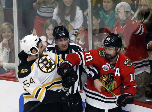 A referee tries to break up a fight as Boston Bruins defenseman Adam McQuaid &#40;54&#41; goes after Chicago Blackhawks center Patrick Sharp &#40;10&#41; during the second period of Game 1 in their NHL Stanley Cup Final hockey series,Wednesday, June 12, 2013 in Chicago. &#40;AP Photo&#47;Charles Rex Arbogast&#41; <span class=meta>(AP Photo&#47; Charles Rex Arbogast)</span>