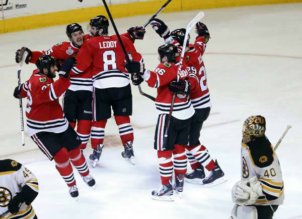 Chicago Blackhawks center Andrew Shaw, second from left, celebrates with his teammates after scoring the winning goal during the third overtime period of Game 1 in their NHL Stanley Cup Final hockey series against the Boston Bruins, Thursday, June 13, 2013, in Chicago. The Blackhawks won 4-3. &#40;AP Photo&#47;Charles Rex Arbogast&#41; <span class=meta>(AP Photo&#47; Charles Rex Arbogast)</span>