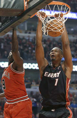 Miami Heat center Chris Bosh, right, dunks against Chicago Bulls forward Luol Deng during the first half of an NBA basketball game in Chicago on Wednesday, March 27, 2013. &#40;AP Photo&#47;Nam Y. Huh&#41; <span class=meta>(AP Photo&#47; Nam Y. Huh)</span>