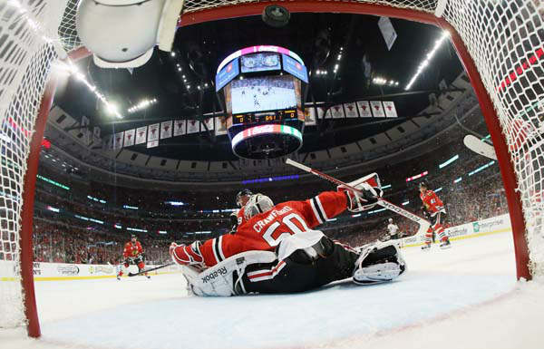 The puck flies into the net as Chicago Blackhawks goalie Corey Crawford &#40;50&#41; gives up a goal by Boston Bruins left wing Milan Lucic during the first period of Game 1 in their NHL Stanley Cup Final hockey series, Wednesday, June 12, 2013, in Chicago. &#40;AP Photo&#47;Bruce Bennett, Pool&#41; <span class=meta>(AP Photo&#47; Bruce Bennett)</span>