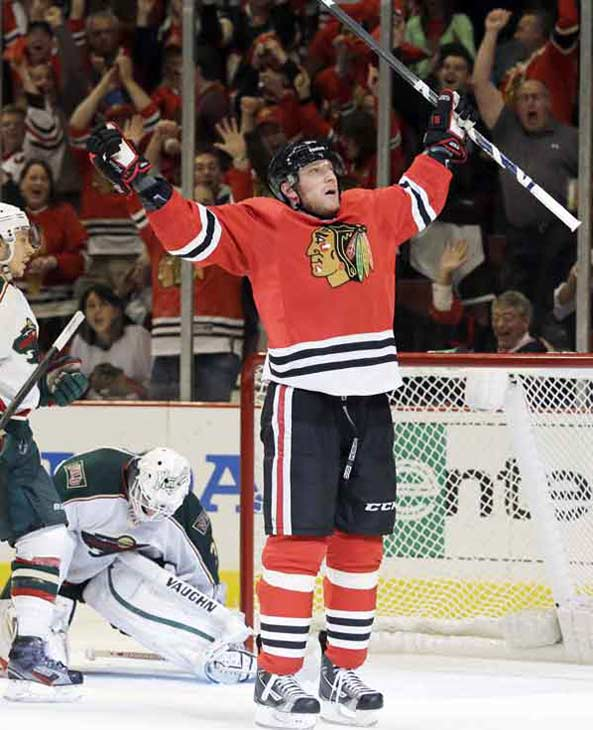 Chicago Blackhawks' Marian Hossa, right, celebrates after scoring his second goal as Minnesota Wild goalie Josh Harding (37) and Jared Spurgeon (46) react during the second period of Game 5 of an NHL hockey Stanley Cup first-round playoff series in Chicago, Thursday, May 9, 2013. (AP Photo/Nam Y. Huh)