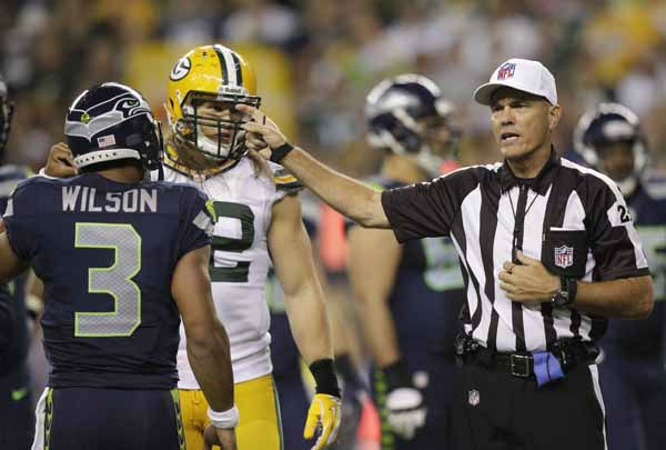 Seattle Seahawks Russell Wilson and Green Bay Packers Clay Matthews &#40;52&#41; watch as an official makes a call during the game against the Seattle Seahawks in the second half of an NFL football game, Monday, Sept. 24, 2012, in Seattle. &#40;AP Photo&#47;Stephen Brashear&#41; <span class=meta>(AP Photo&#47; Stephen Brashear)</span>
