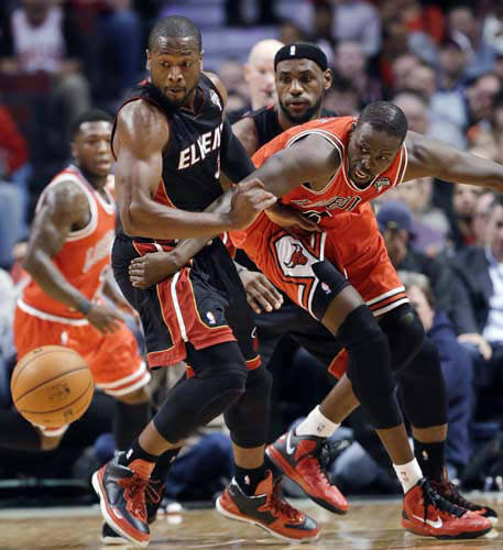 Miami Heat guard Dwyane Wade, left, forward LeBron James, center, and Chicago Bulls forward Luol Deng watch a loose ball during the first half of an NBA basketball game in Chicago on Wednesday, March 27, 2013. &#40;AP Photo&#47;Nam Y. Huh&#41; <span class=meta>(AP Photo&#47; Nam Y. Huh)</span>