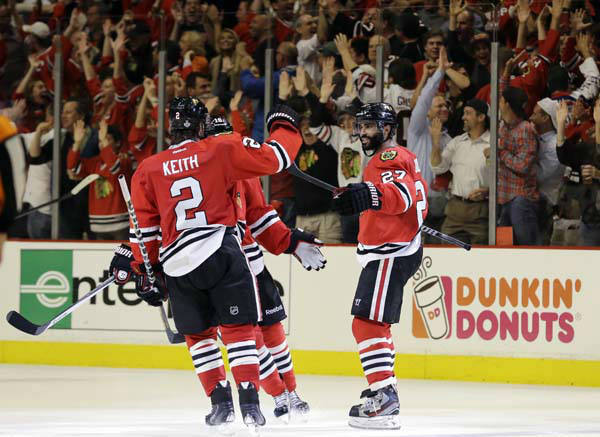 Chicago Blackhawks defenseman Johnny Oduya, right, celebrates with his teammates after scoring a goal against the Boston Bruins during the third period of Game 1 in their NHL Stanley Cup Final hockey series on Wednesday, June 12, 2013, in Chicago. &#40;AP Photo&#47;Nam Y. Huh&#41; <span class=meta>(AP Photo&#47; Nam Y. Huh)</span>