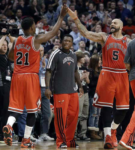 Chicago Bulls guard Jimmy Butler, left, celebrates with forward Carlos Boozer after scoring a basket, as Nate Robinson, center, watches during the second half of an NBA basketball game against the Miami Heat in Chicago on Wednesday, March 27, 2013. The Bulls won 101-97, ending the Heat&#39;s 27-game winning streak. &#40;AP Photo&#47;Nam Y. Huh&#41; <span class=meta>(AP Photo&#47; Nam Y. Huh)</span>