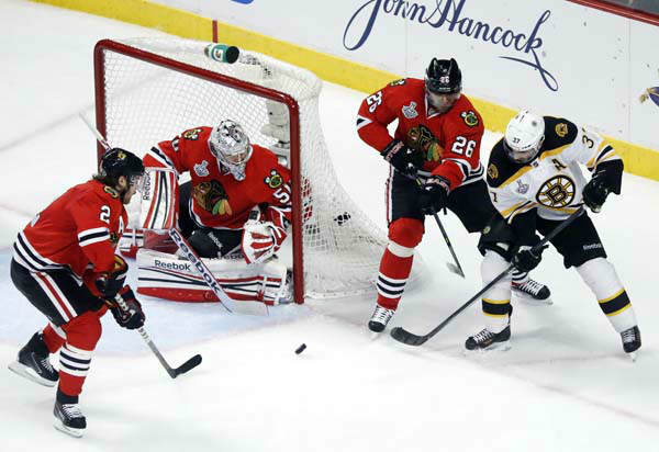 Boston Bruins center Patrice Bergeron &#40;37&#41; takes a shot against Chicago Blackhawks defenseman Duncan Keith &#40;2&#41;, goalie Corey Crawford &#40;50&#41; and center Michal Handzus &#40;26&#41; during the first period of Game 1 in their NHL Stanley Cup Final hockey series on Wednesday, June 12, 2013, in Chicago. &#40;AP Photo&#47;Charles Rex Arbogast&#41; <span class=meta>(AP Photo&#47; Charles Rex Arbogast)</span>