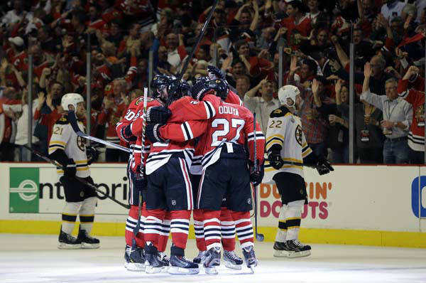 Chicago Blackhawks defenseman Johnny Oduya &#40;27&#41; celebrates with his teammates after scoring a goal against the Boston Bruins during the third period of Game 1 in their NHL Stanley Cup Final hockey series, Wednesday, June 12, 2013, in Chicago. &#40;AP Photo&#47;Nam Y. Huh&#41; <span class=meta>(AP Photo&#47; Nam Y. Huh)</span>