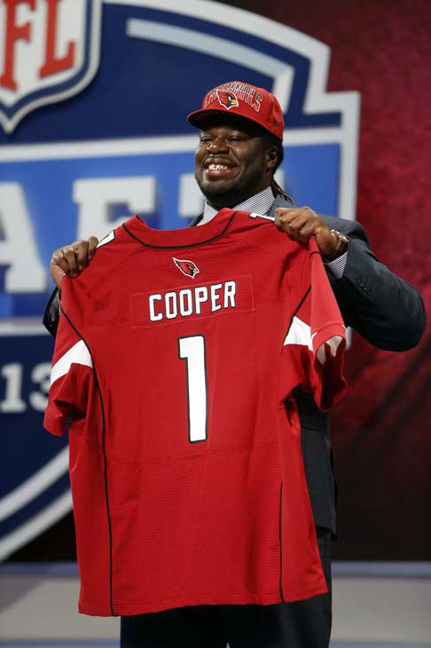 Jonathan Cooper from North Carolina holds up the team jersey after being selected seventh overall by the Arizona Cardinals in the first round of the NFL football draft, Thursday, April 25, 2013 at Radio City Music Hall in New York.  &#40;AP Photo&#47;Jason DeCrow&#41; <span class=meta>(AP Photo&#47; Jason DeCrow)</span>