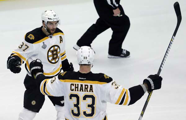 Boston Bruins center Patrice Bergeron &#40;37&#41; celebrates with defenseman Zdeno Chara &#40;33&#41; after scoring a goal against the Chicago Blackhawks during the third period of Game 1 in their NHL Stanley Cup Final hockey series, Wednesday, June 12, 2013, in Chicago. &#40;AP Photo&#47;Charles Rex Arbogast&#41; <span class=meta>(AP Photo&#47; Charles Rex Arbogast)</span>
