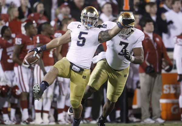 Notre Dame linebacker Manti Te&#39;o &#40;5&#41;celebrates with teammate Stephon Tuitt &#40;7&#41; after an interception against Oklahoma in the fourth quarter of an NCAA college football game in Norman, Okla., Saturday, Oct. 27, 2012. &#40;AP Photo&#47;Sue Ogrocki&#41; <span class=meta>(AP Photo&#47; Sue Ogrocki)</span>