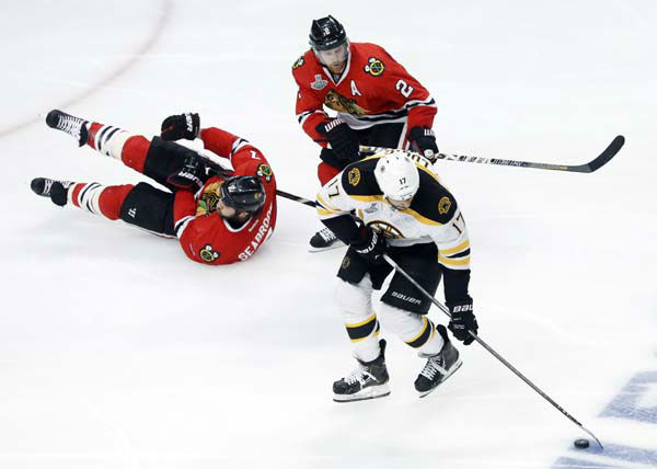 Boston Bruins left wing Milan Lucic &#40;17&#41; controls the puck against Chicago Blackhawks defensemen Brent Seabrook &#40;7&#41; and Duncan Keith &#40;2&#41; during the second period of Game 1 in their NHL Stanley Cup Final hockey series on Wednesday, June 12, 2013, in Chicago. &#40;AP Photo&#47;Charles Rex Arbogast&#41; <span class=meta>(AP Photo&#47; Charles Rex Arbogast)</span>