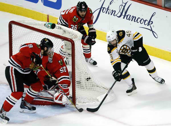 Chicago Blackhawks defenseman Nick Leddy &#40;8&#41; and goalie Corey Crawford &#40;50&#41; make a save on a shot by Boston Bruins center Rich Peverley &#40;49&#41; during the first period of Game 1 in their NHL Stanley Cup Final hockey series,Wednesday, June 12, 2013 in Chicago. &#40;AP Photo&#47;Charles Rex Arbogast&#41; <span class=meta>(AP Photo&#47; Charles Rex Arbogast)</span>