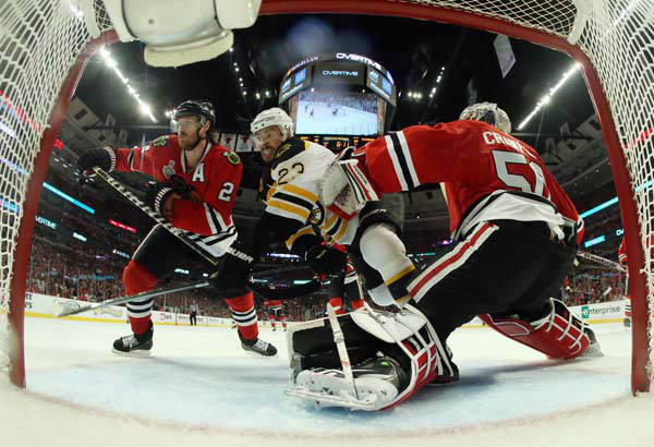 Chicago Blackhawks defenseman Duncan Keith &#40;2&#41; and goalie Corey Crawford &#40;50&#41; battle for the control of the puck against Boston Bruins center Chris Kelly &#40;23&#41; during the second overtime period of Game 1 in their NHL Stanley Cup Final hockey series, Wednesday, June 12, 2013, in Chicago. &#40;AP Photo&#47;Bruce Bennett, Pool&#41; <span class=meta>(AP Photo&#47; Bruce Bennett)</span>