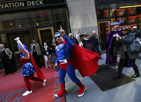 "<div class=""meta ""><span class=""caption-text "">New York Giants fans, from left, Eric Maybee and Kathleen O'Connor and Minnesota Vikings fans Lisa and John Maranzana wave outside Radio City Music Hall before the first round of the NFL football draft on Thursday, April 25, 2013, in New York. (AP Photo/Jason DeCrow) (AP Photo/ JASON DECROW)</span></div>"