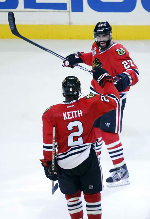 Chicago Blackhawks defenseman Johnny Oduya &#40;27&#41; celebrates his goal with defenseman Duncan Keith &#40;2&#41; during the third period of Game 1 in their NHL Stanley Cup Final hockey series against the Boston Bruins,Wednesday, June 12, 2013, in Chicago. &#40;AP Photo&#47;Charles Rex Arbogast&#41; <span class=meta>(AP Photo&#47; Charles Rex Arbogast)</span>