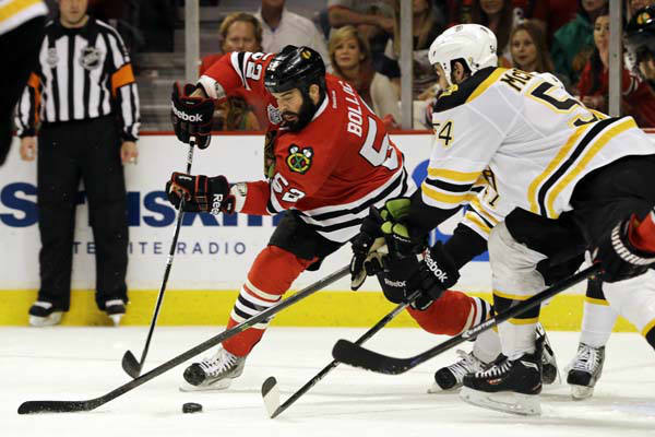 Chicago Blackhawks left wing Brandon Bollig &#40;52&#41; controls the puck against Boston Bruins defenseman Adam McQuaid &#40;54&#41; and Torey Krug during the second period of Game 1 in their NHL Stanley Cup Final hockey series, Wednesday, June 12, 2013, in Chicago. &#40;AP Photo&#47;Nam Y. Huh&#41; <span class=meta>(AP Photo&#47; Nam Y. Huh)</span>