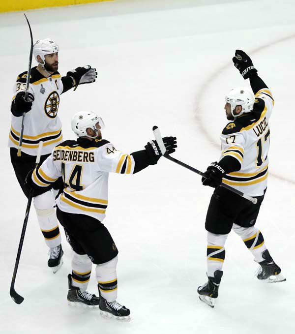 Boston Bruins left wing Milan Lucic &#40;17&#41; celebrates with defensemen Zdeno Chara &#40;33&#41; and Dennis Seidenberg &#40;44&#41; after scoring a goal against the Chicago Blackhawks during the first period of Game 1 in their NHL Stanley Cup Final hockey series on Wednesday, June 12, 2013, in Chicago. &#40;AP Photo&#47;Charles Rex Arbogast&#41; <span class=meta>(AP Photo&#47; Charles Rex Arbogast)</span>