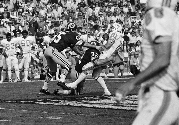 Miami Dolphins&#39; Jim Kiick &#40;21&#41; is tackled by Washington Redskins&#39; Jack Pardee &#40;32&#41; and Chris Hanburger &#40;55&#41; after taking in a Bill Kilmer pass on the 50-year line during second quarter of Super Bowl game in Los Angeles on Jan. 14, 1973. &#40;AP Photo&#41; <span class=meta>(AP Photo&#47; Anonymous)</span>