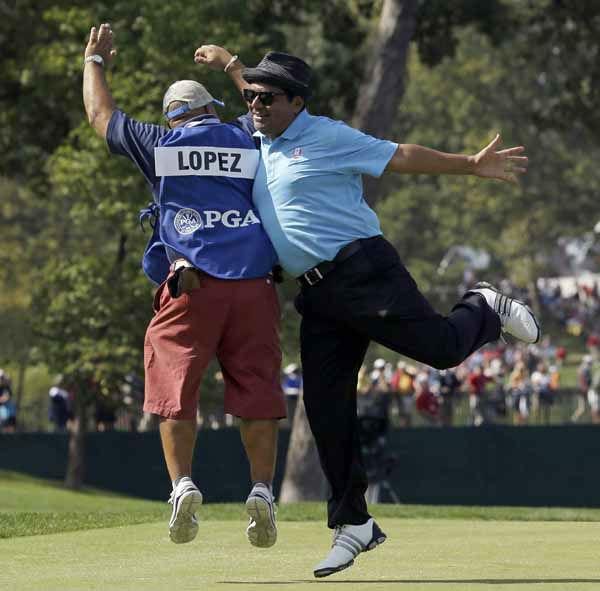 Comedian George Lopez, right, celebrates with his caddie Michael Collins after making a putt on the second hole during a celebrity scramble event at the Ryder Cup PGA golf tournament Tuesday, Sept. 25, 2012, at the Medinah Country Club in Medinah, Ill. &#40;AP Photo&#47;David J. Phillip&#41; <span class=meta>(AP Photo&#47; David J. Phillip)</span>