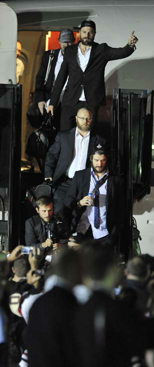"<div class=""meta ""><span class=""caption-text "">Members of the Stanley Cup winning Chicago Blackhawks are greeted after arriving at O'Hare International Airport in Chicago, on Tuesday, June 25, 2013. The Chicago Blackhawks landed home with the Stanley Cup just before dawn Tuesday morning and were greeted on the tarmac with a water cannon salute, about a dozen fire trucks and even more police cars _ all with their lights flashing. (AP Photo/Paul Beaty) (AP Photo/ PAUL BEATY)</span></div>"