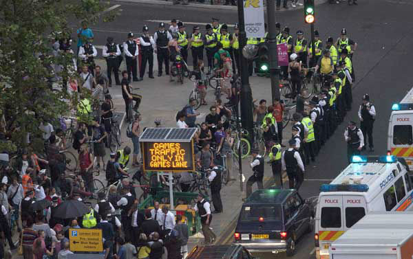 Police surround part of a group of protesting cyclists who tried to block traffic with a mass cycle ride on a road outside the Olympic Park during the Opening Ceremony of the 2012 Summer Olympics, Friday, July 27, 2012, in London. &#40;AP Photo&#47;Ben Curtis&#41; <span class=meta>(AP Photo&#47; Ben Curtis)</span>