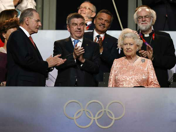 The President of the International Olympic Committee Jacques Rogge, left, and Britain&#39;s Archbishop of Canterbury Rowan Williams, back right, applaud as Britain&#39;s Queen Elizabeth II, foreground right, arrives during the Opening Ceremony at the 2012 Summer Olympics, Friday, July 27, 2012, in London. &#40;AP Photo&#47;Matt Dunham&#41; <span class=meta>(AP Photo&#47; Matt Dunham)</span>